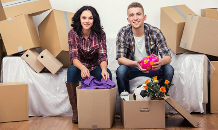 happy couple packing their possessions in cardboard boxes