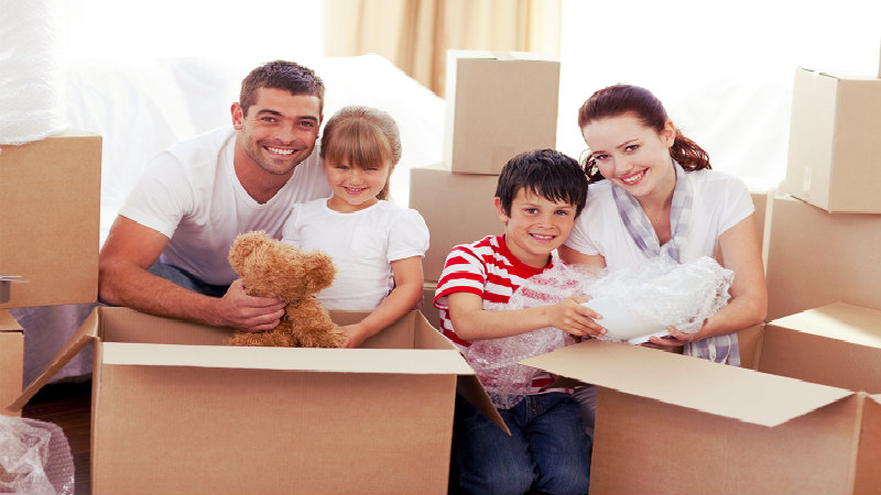 happy family of four packing some toys in cardboard boxes