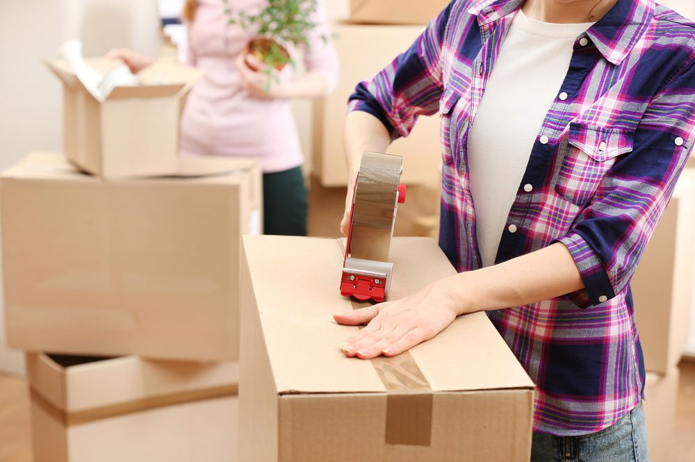 cropped image of a woman securing a box with tape