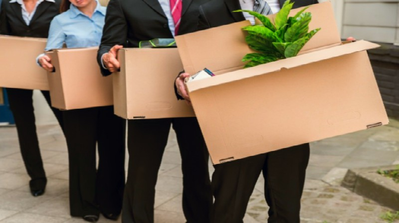 office staff in formals carrying out packed boxes out of the premise