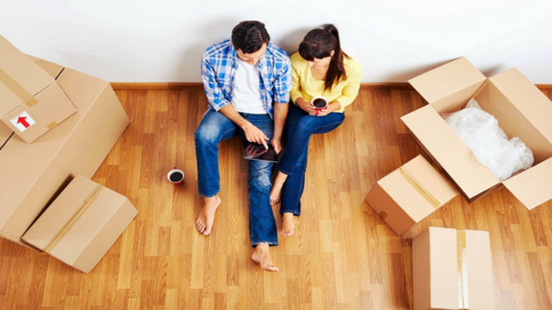 young couple sitting on the floor and looking in the I Pad while some cardboard boxes lay on the floor