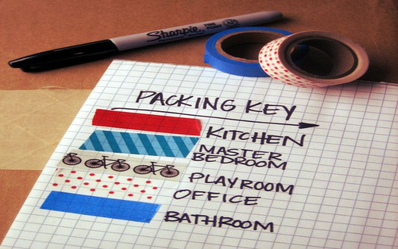 happy couple sitting on a couch with some cardboard boxes around them