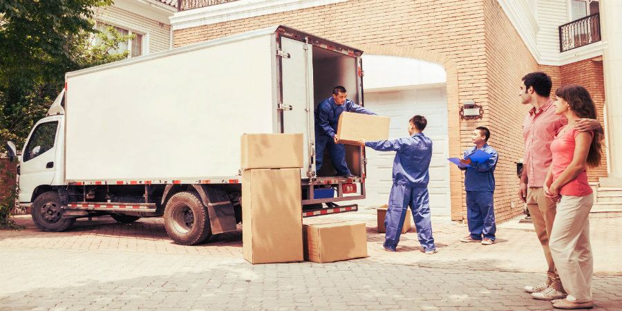 three removalists load some boxes in a truck while a young couple look over