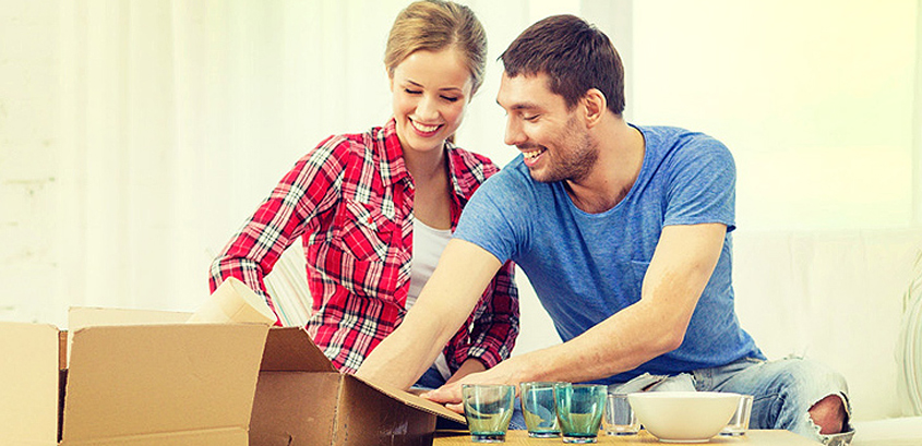 happy couple packing glassware in boxes