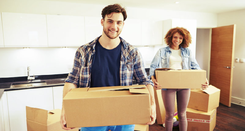 happy man and woman carrying packed boxes out of the property