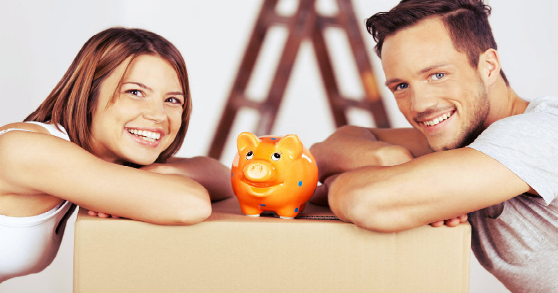 young couple happy to save money during the move with a piggy bank kept in between them