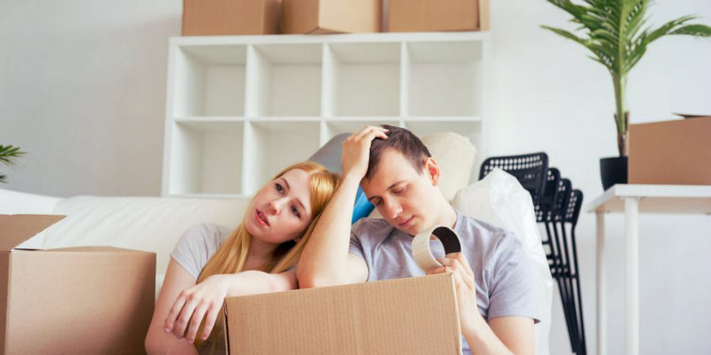 worried couple sitting on the floor with packing boxes around them