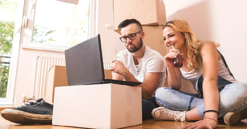happy couple looking for a removalist online while some packed boxes are kept behind them