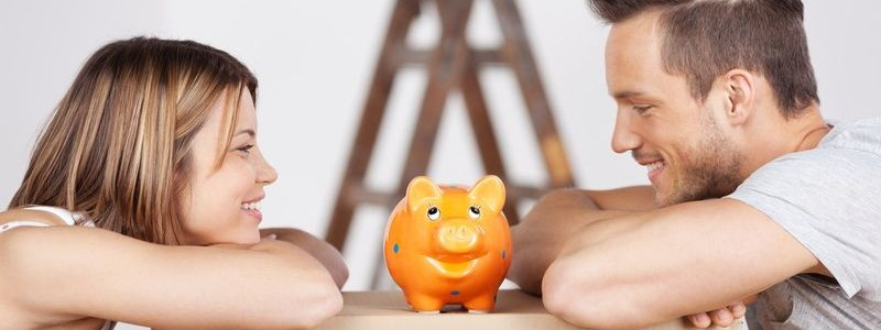 a couple is looking toward a piggy bank