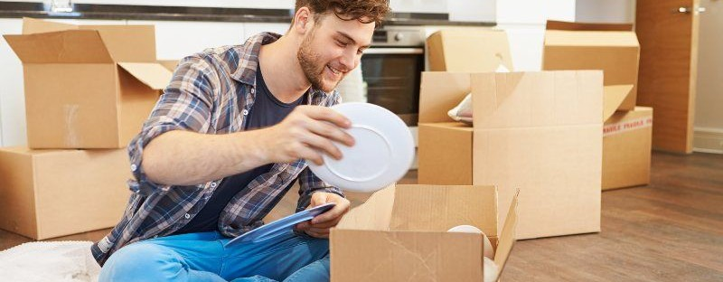 young man packing crookery in a cardboard box