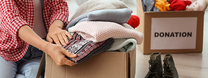 Young woman packing old household items for donation