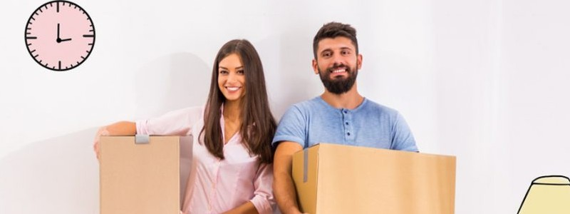 young couple holding cardboard boxes preparing for a house relocation