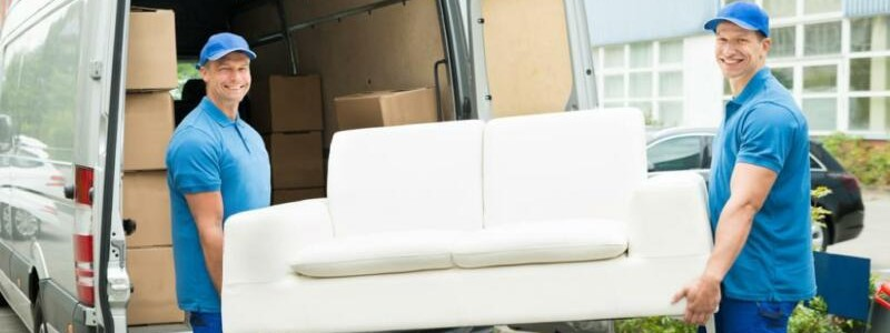 young professionals loading a couch in a truck
