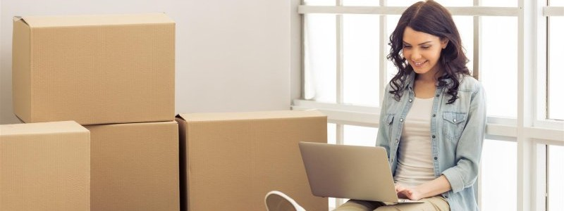 young woman with a laptop preparing for a relocation