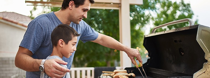 young father is grilling food with his son
